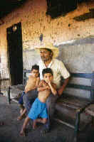 Acompanied by two little ones, a Balsamo campesino rests on the porch of his ranch.